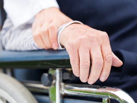 Hands of an elderly woman resting on the wheelchair photo