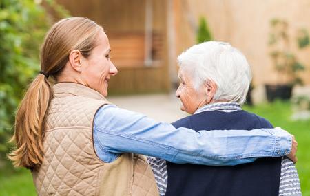an elderly person: Cuidador joven que recorre con la mujer mayor en el parque
