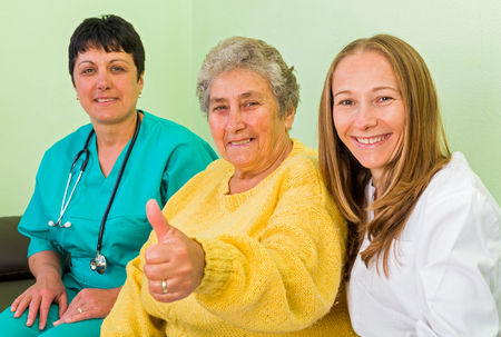 aide: Elderly woman with her carer and doctor