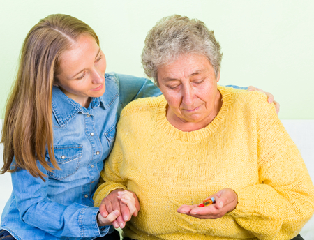 Young carer helping the elderly woman to take the pills