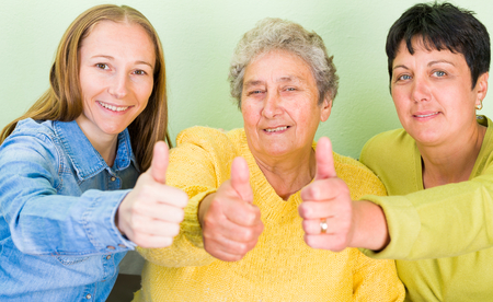 aide: Photo of elderly woman with her daughters showing thumbs up Stock Photo