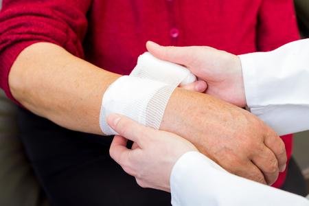 gauze: Photo of doctor bandaging the elderly woman wrist Stock Photo