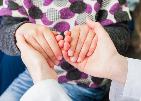 Foto di giovane medico mani che tengono la mano del bambino