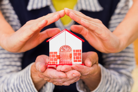 geriatric care: Photo of a miniature house holding in hands