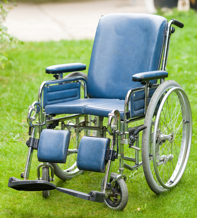 disablement: Photo of a wheelchair on green grass