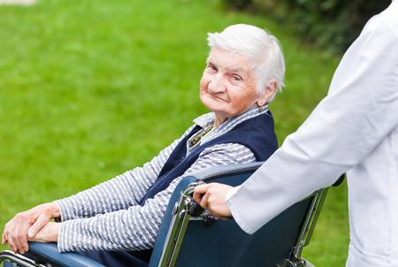 Foto van jonge mantelzorger duwen de oudere vrouw in rolstoel Stockfoto