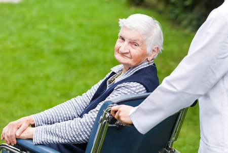 old age care: Photo of young carer pushing the elderly woman in wheelchair