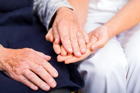 Giovane medico dando aiutando mani di donna anziana