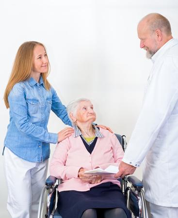 Foto van de bejaarde vrouw met haar kleinkind bij de dokter