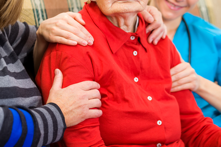 supported: Photo of elderly woman supported by family
