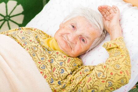 mentally ill: Sweet smiling elderly woman resting in bed Stock Photo
