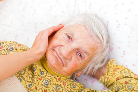 caresses: Sweet smiling elderly woman resting in bed Stock Photo