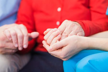 Jeune soignant donnant mains secourables pour femme âgée Banque d'images