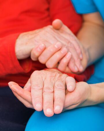 Young doctor giving helping hands for elderly woman photo