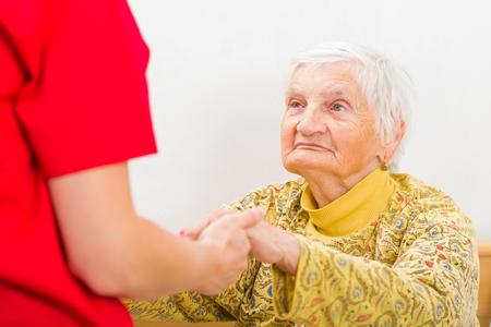 Junge Pfleger geben helfende Hände für die ältere Frau Standard-Bild - 37013642
