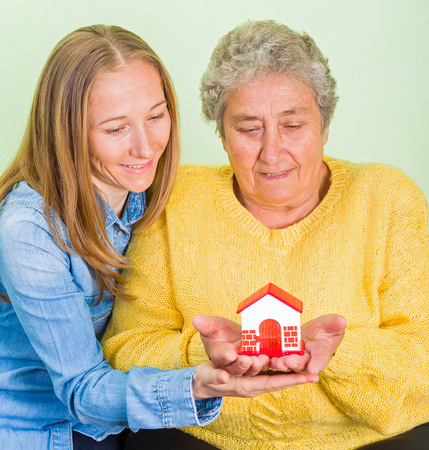 carers: Elderly woman and daughter holding a miniature house in hands