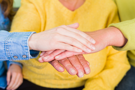 geriatrics: Photo of elderly woman hands supported by young carer Stock Photo