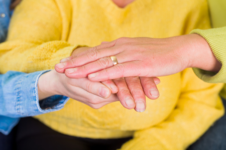 caring hands: Photo of elderly woman hands supported by young carer Stock Photo