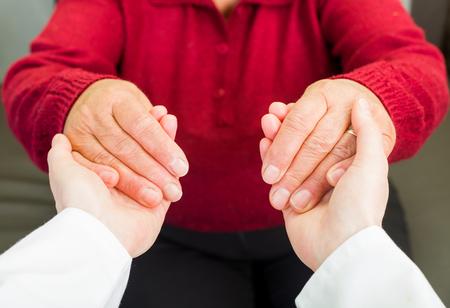 persona de la tercera edad: Cuidador joven que da la mano de ayuda para la mujer de edad avanzada