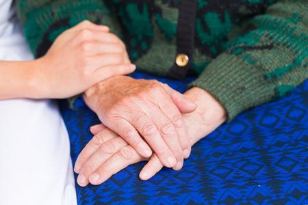Giovane assistente dando aiutando mani di donna anziana