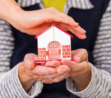 geriatrics: Photo of a miniature house holding in hands