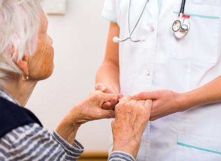 Junger Arzt gibt helfende Hände für ältere Frau