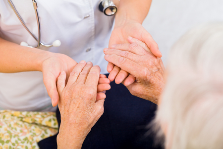 aide: Young doctor giving helping hands for elderly woman