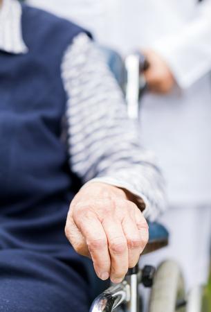 車椅子に高齢者女性の手