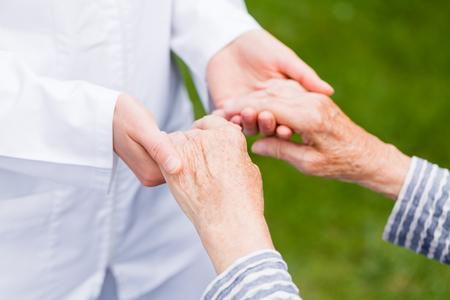 Cuidador joven que da la mano de ayuda para la mujer de edad avanzada Foto de archivo - 37849279