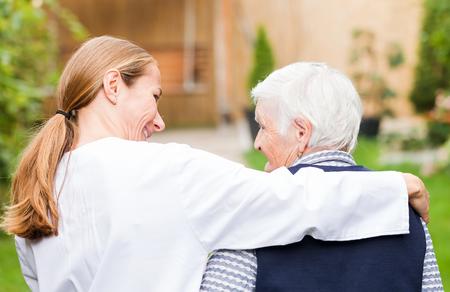 enfermedades mentales: Cuidador joven que recorre con la mujer mayor en el parque