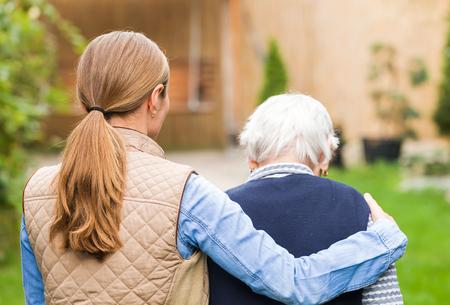 Cuidador joven que recorre con la mujer mayor en el parque Foto de archivo