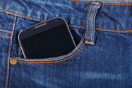 Mobile phone in the pocket of blue jeans photo