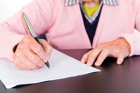 Foto van de bejaarde vrouw die is het schrijven van een brief Stockfoto