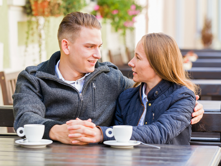 coquetry: Photo of young couple talking and drinking coffee