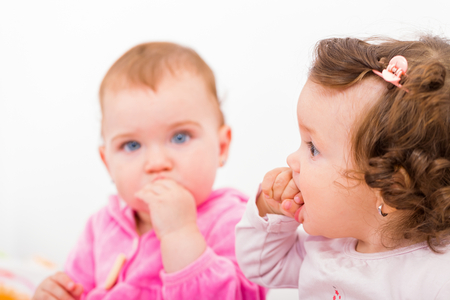 Photo of two adorable baby sitting on the bed and nibbles Stock Photo