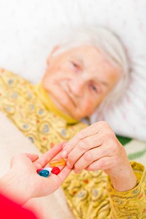 Photo of elderly woman taking the medication 版權商用圖片 - 64719835