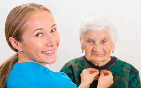 assisting: Photo of elderly woman dressed by the carer