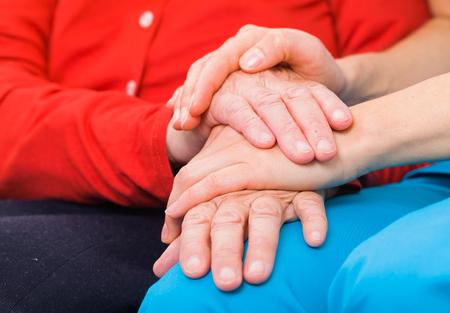 enfermedades mentales: Médico joven que da la mano de ayuda para la mujer de edad avanzada