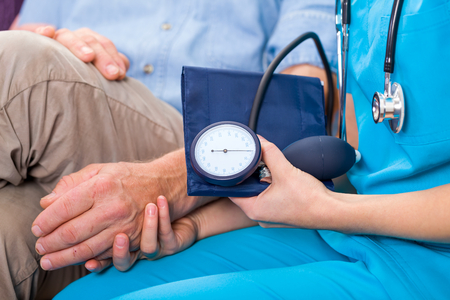 blood pressure monitor: Photo of young doctor measures the blood pressure
