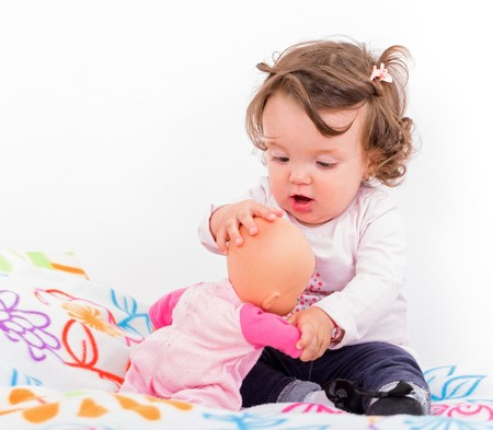 baby doll: Adorable baby girl sitting on the bed and playing with doll