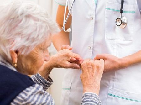 ayudando: Médico joven que da la mano de ayuda para la mujer de edad avanzada