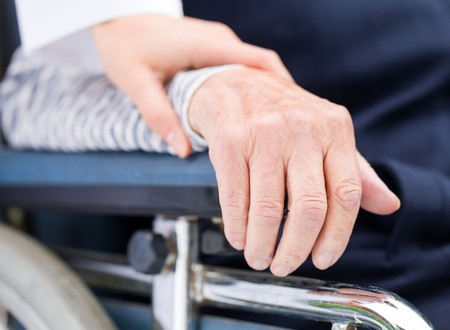 an elderly person: Hands of an elderly woman resting on the wheelchair Stock Photo