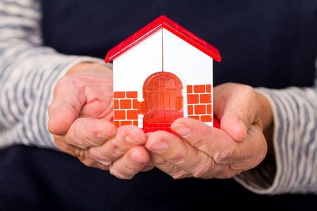 retirement homes: Close up photo of miniature house holding in hands