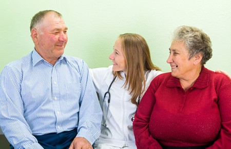 aide: Photo of happy elderly couple with the young doctor
