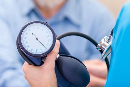 hipertension: Foto de joven médico mide la presión arterial Foto de archivo