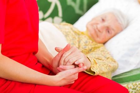 helping: Cuidador joven que da la mano amiga de la mujer de edad avanzada Foto de archivo