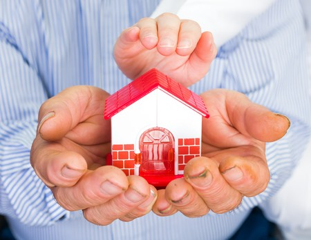 householder: Photo of a miniature house holding in hands