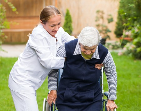 高齢者の女性を助ける若い介護者の写真