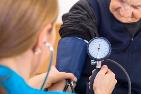 aide: Young doctor measures the elderly woman blood pressure