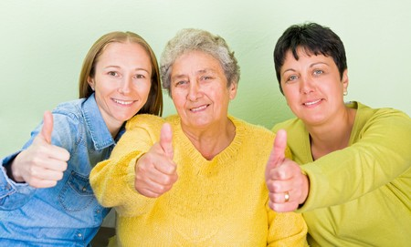 geriatrics: Photo of elderly woman with her daughters showing thumbs up Stock Photo